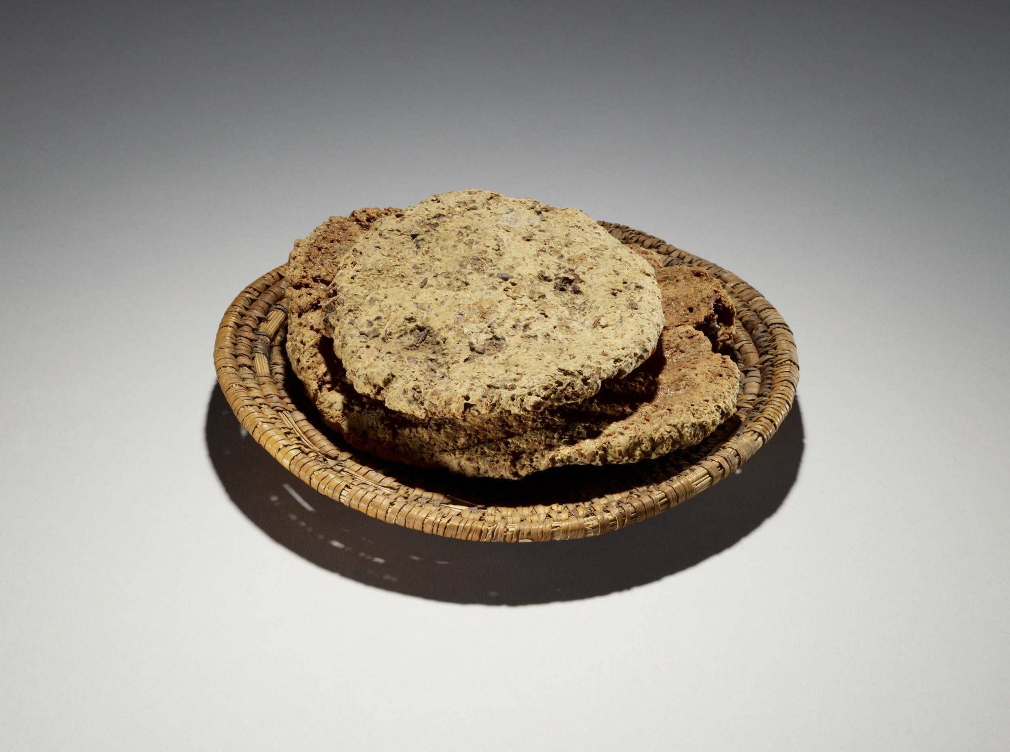 Dish of woven palm leaf, with two loaves of unleavened bread. One piece of bread has hand imprints on both sides of the loaf, probably left by the baker. From Thebes, Egypt. British Museum, EA5341.
