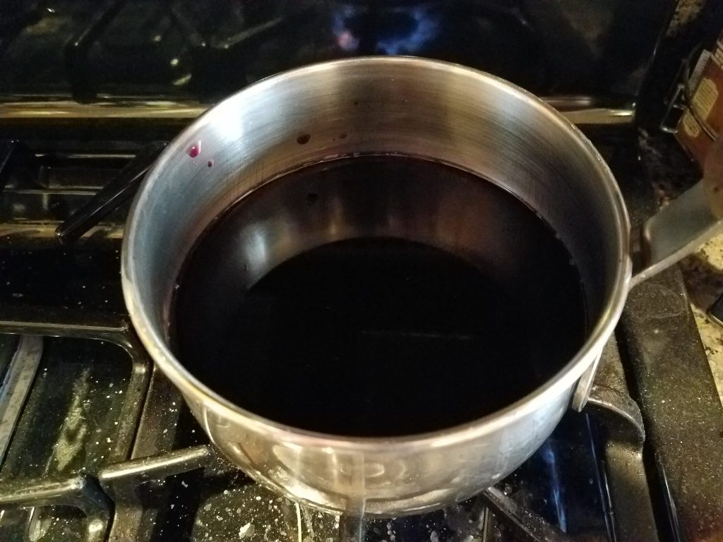 Red Concord Kedem Grape Juice boiling in a pot.